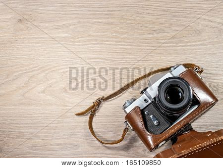 Old film camera in a brown leather case photographed on wood background. The camera lens is up.