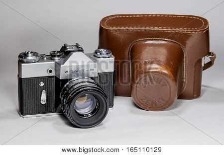 Gatchina, Russia - January 14, 2017: The old Soviet film camera Zenit. Photographed on a bright background. To the right of the camera is its leather case.