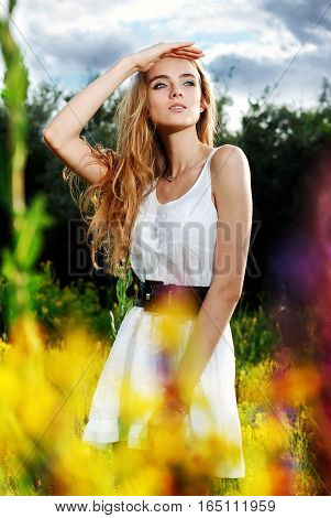 Young woman standing in a flower glade and looking into the distance.