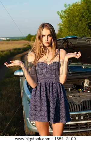 confused girl did not know what to do with a car that broke down in a field