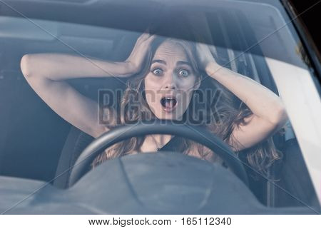 Young woman with hands on eyes sitting scared in car