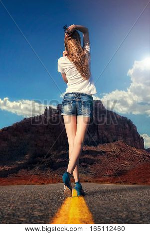 attractive girl walking along the road in the desert under the scorching sun