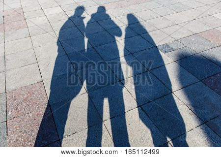 The shadows of three people on a pavement of tiles.