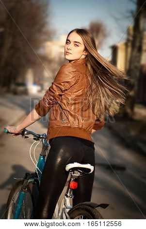 Portrait of pretty young woman with bicycle in a city road