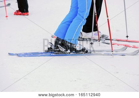 Closeup to the foot of the skier wearing ski on the snow.