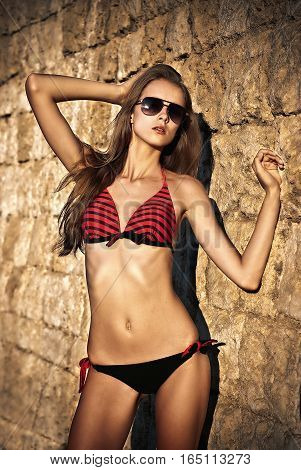 graceful beautiful girl fashion model posing against a stone wall in a swimsuit
