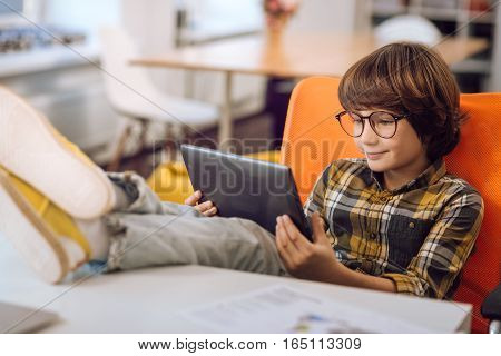 It is exciting. Little nice boy smiling while looking on tablet watching for something getting pleasance wearing checked shirt and glasses