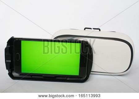 Virtual reality, VR, helmet and smartphone with green screen for key chroma screen, On a white background