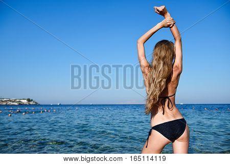 Beautiful young woman in bikini on the sunny beach standing in the water
