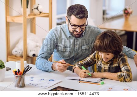 Enjoy your weekend. Delighted boy holding fet-tip pen in the right hand while doing notes sitting near his father