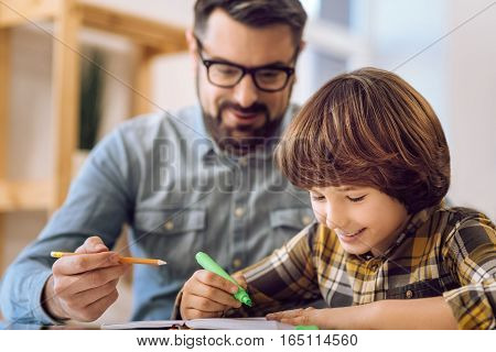 Like to draw. Little boy making notes in copybook feeling happiness while spending time with father