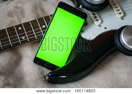 Smartphone with green screen on an Electric Guitars guitar