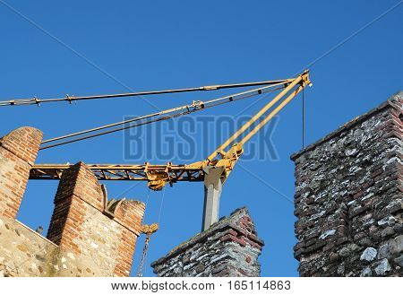 medieval castle at construction .detail during reconstruction with help of a heavy crane .
