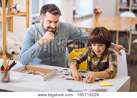 Positive delighted man wearing jeans shirt keeping his hand on the chic while looking at his playing son