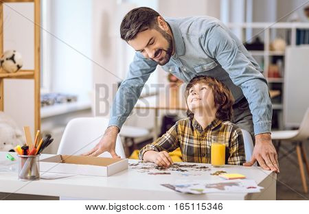 Happy smiling boy keeping his head upwards while looking at his father playing with puzzles