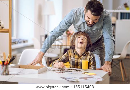 Love you dad. Positive delighted man wearing jeans shirt standing behind son while looking at him