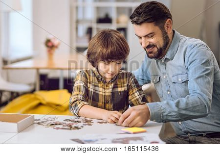 Smile and do. Smiling father sitting near his son holding puzzle in his hand while watching the process