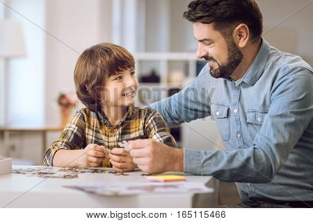 I am happy. Positive bearded male wearing jeans shirt holding puzzle looking at his son