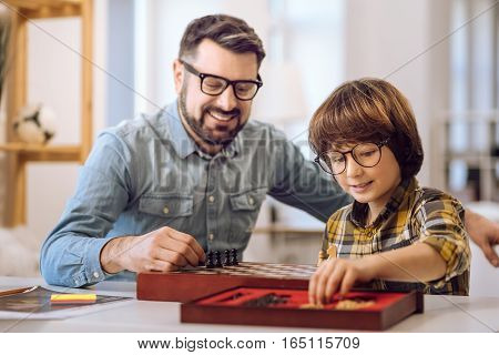 play with pleasure. Little intelligent boy wearing spectacles holding pawn in his left hand while preparing for game