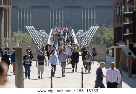 LONDON, UK - SEPTEMBER 10, 2015: Millennium bridge with lots of people walking against of St. Paul s cathedral