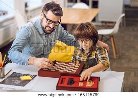 Family day. Little smart boy wearing spectacles holding pawn in his left hand while preparing for game