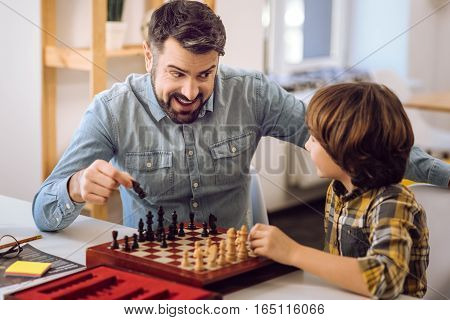 Good choice. Serious boy wearing checked shirt holding pawn in his left hand while looking at it