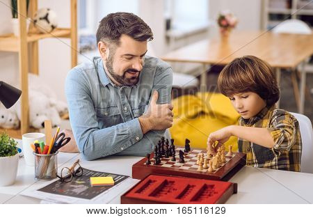 Best move. Intelligent pupil wearing checked shirt holding pawn in his left hand while looking at it