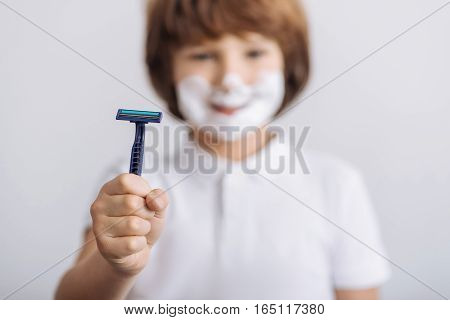 It is danger for children. Kind male-child wearing white shirt holding blue razor in his right hand while looking at camera