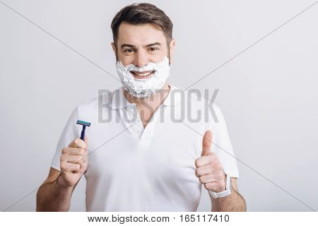 qualitative razor. Young smiling father wearing white shirt holding blue razor in his right hand while looking at camera