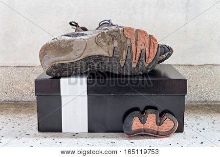 Old sport shoes on paper box and terrazzo floor