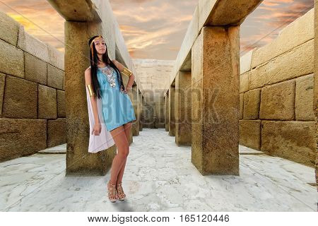 Pretty woman in egyptian queen costume near colonnade of valley temple of khafre, on the bottom of the causeway from the sphinx to the Great pyramid