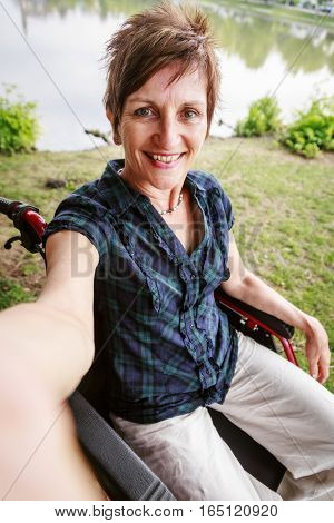 Senior woman in wheelchair, taking a selfie with her phone.