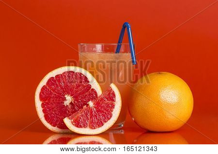 Whole red grapefruit cross section and a slice placed next to a glass of grapefruit juice with drinking straw isolated on red background. Focus stacked image