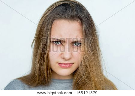 Portrait of beautiful teenager girl emotional posing on white background isolated. Angry, evil, rude