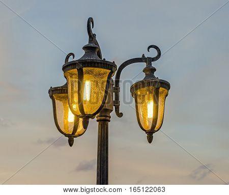 Light pole with three bulbs orange light blue sky close up outdoor