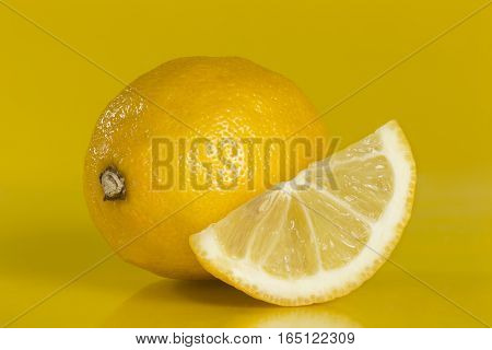 Studio shot of a whole and a slice of lemon fruit isolated on yellow background. Focus stacked image