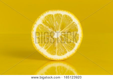 Close up of a juicy lemon fruit cross section isolated on yellow background