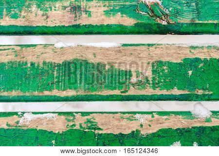 Background picture made of three old green wood boards covered snow