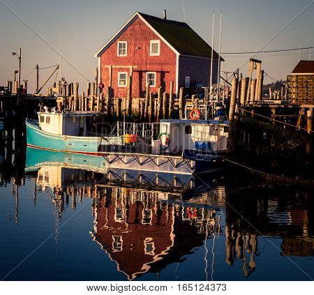 Fishing boat and buildings reflecting in a harbour