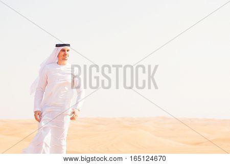 young arabian man posing in the desert