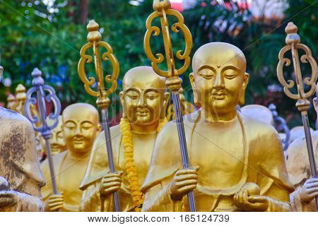Golden Buddha statues along the stairs leading to the Ten Thousand Buddhas Monastery and landscape with green trees in the background in Thailand