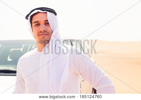 young arabian man in the desert, standing next to his SUV