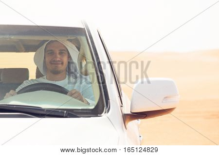 young arabian man in the desert, driving his SUV