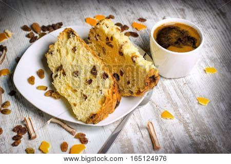 Fruit cake with raisins, candied fruit and coffee on rustic table