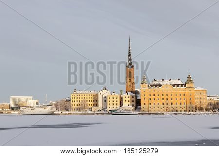 STOCKHOLM - JAN 08 2017: Beautiful old buildings at Riddarholmen a cold winter morning ice on the sea. January 08 2017 in Stockholm Sweden