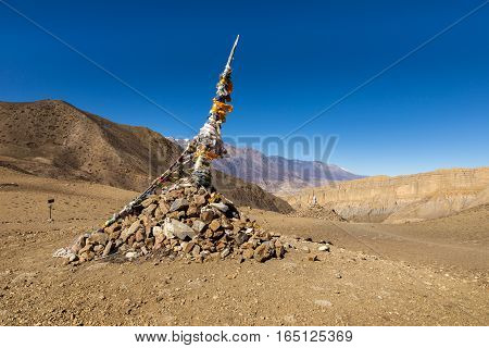 Traditional Tibetan pile of stones and colored flags on the pass, Himalayas, Nepal.