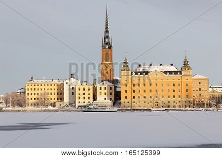 STOCKHOLM - JAN 08 2017: Beautiful yellow old buildings and a church at Riddarholmen a cold winter morning ice on the sea. January 08 2017 in Stockholm Sweden