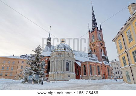 STOCKHOLM - JAN 08 2017: The Riddarholm church in Riddarholmen in central Stockholm a cold winter morning snow on the ground. January 08 2017 in Stockholm Sweden