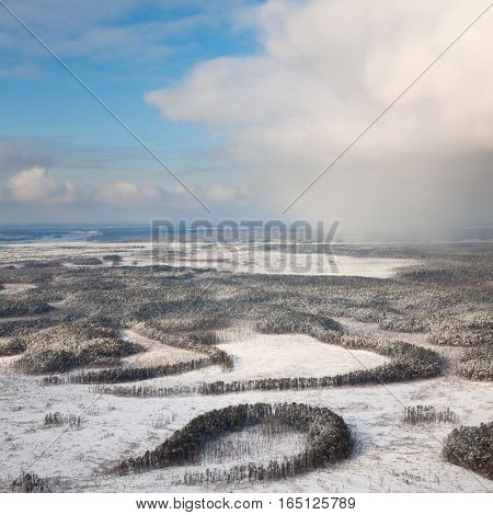 Aerial view of winter woodlands during a flight at frosty day.