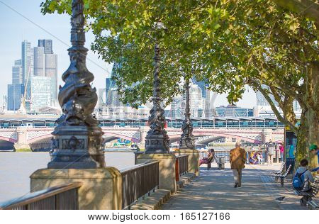 LONDON, UK - SEPTEMBER 10, 2015: Embankment of River Thames with lots of walking people